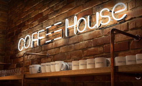 Półka z kubkami i napis Coffee House